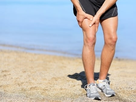 28636105 - muscle injury. runner man with sprain thigh muscle. athlete in sports shorts clutching his thigh muscles after pulling or straining them while jogging on the beach wearing running shoes.