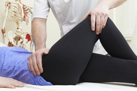 47366824 - male osteopath treating female patient with hip problem